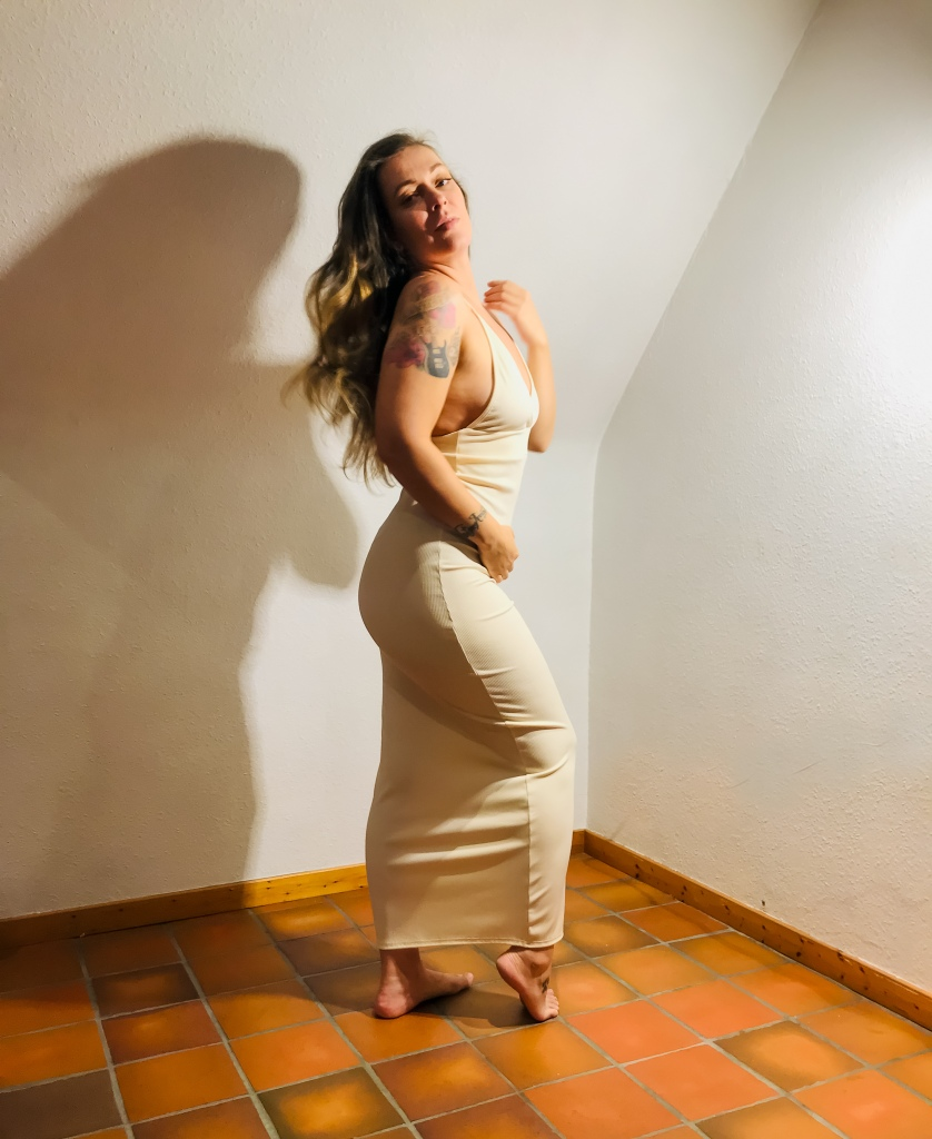 Barbara Fava wearing a creamy white dress with straps. She is posing sideway. Long hair on her back. Barefoot.