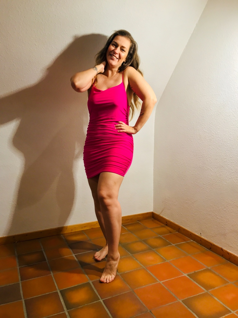 Barbara Fava smiling and wearing a hot pink midi dress by the company Femme Luxe.